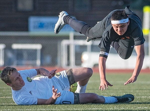 Panther midfielder Ernie Acevedo goes airborne Tuesday afternoon after a hard tackle by Cody's Nic Nieters at Cody High School. The Broncs upended their cross-county rivals 2-0.
