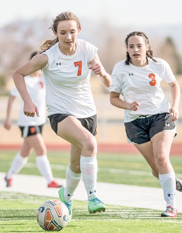 Lady Panthers forward Malia Hedges pushes the ball up the pitch, backed by teammate Jaclyn Haire, during Monday's game against Worland at Panther Stadium. The Lady Warriors avenged an earlier season loss to Powell, winning 3-1.