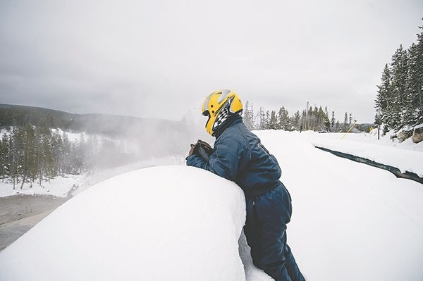 A winter tourist checks out the views in Yellowstone National Park while on a snowmobile tour in February. The Wyoming Legislature recently called on the federal government to charge a fee at Yellowstone and Grand Teton that would be given to states to help manage wildlife.