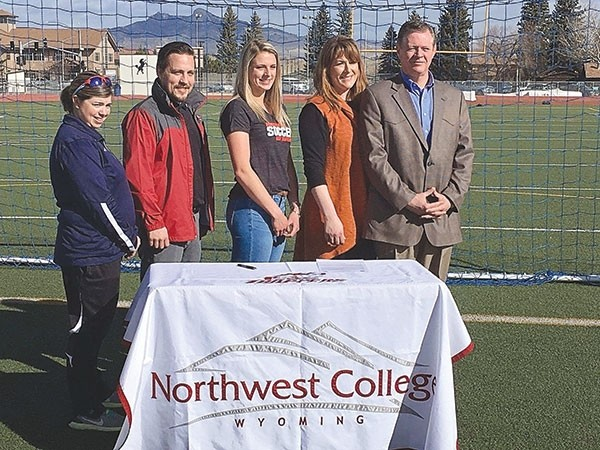 Genevieve Sauers (center) signs her letter of intent to play soccer for NWC during a ceremony last week. From left are Cody High School coach Marian Miears, NWC coach Bobby Peters and Sauers' parents, Jo-el and Bruce.