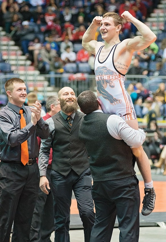 Powell High School junior Reese Karst is held up by head coach Nate Urbach after beating Tristen Kingsley of Torrington by a 5-2 decision to win the 138-pound state championship title.
