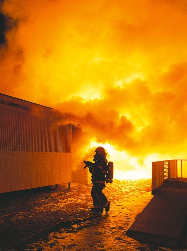 Powell Firefighter Mick Hobbs puts a hose on flames as they shoot out of the back of a trailer in the Cactus Garden Court in Powell Saturday night. The trailer was a total loss and one family pet was lost in the fire.