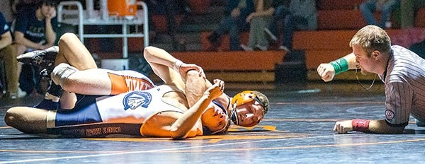 Referee Beau Fulton counts off Powell High School junior Reese Karst's near fall against Jon Sanchez during the 138-pound match of a home dual against Cody on Tuesday, Feb. 6. Karst won by a 16-0 technical fall.