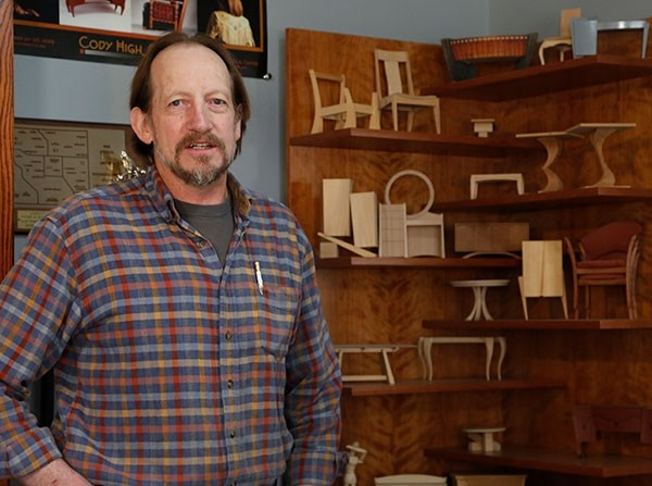 Wood furniture artisan Scott Armstrong of Powell stands near a display of small models of some of the furniture he's made. He makes several models of each piece to see which one he or the customer likes best, then he makes a model to scale before starting the actual furniture. Armstrong is a member of By Western Hands, a group that is working with Northwest College to develop an apprenticeship program and to open a design center in Cody.