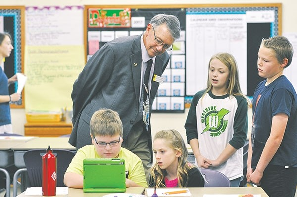 Rep. David Northrup, R-Powell, talks with Caitlin Belmont and Isaac Stensing (standing), who explained their past robotics/coding work and answered legislators' questions during the Hour of Code at Westside Elementary School last month. Third-graders Josh White and Karee Cooley are busy coding at their desks.