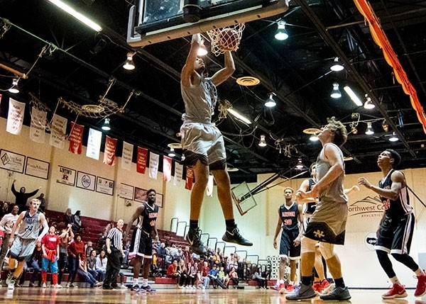 Trappers big man Axel Okongo dunks the ball against Dawson Community College earlier this season, as teammates Blake Hinze, left and Jordan Banks look on. The Trappers fell to Dawson on Friday, 91-73, in Glendive, Montana.
