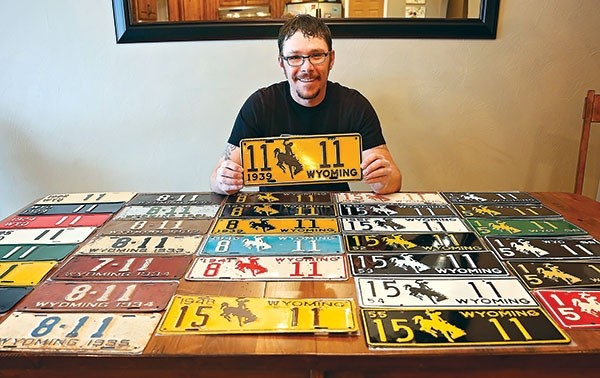 John Stalick holds up his favorite license plate, No. 11-11 from 1939. Stalick's favorite number is 11, and he has several runs of license plate years with the number 11. Those runs come from families who kept the license number, in some cases, for three or more generations.