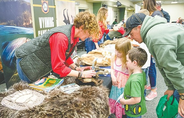 Zack Blain and his two children, Kinzie and Camden, get a lesson on bears from Wyoming Game and Fish Department Hunter and Angler Participation Coordinator Kathryn Boswell during an open house organized by commissioner David Rael at the Lovell Community Center Tuesday. It was the first time the commission held an open house after their meeting.