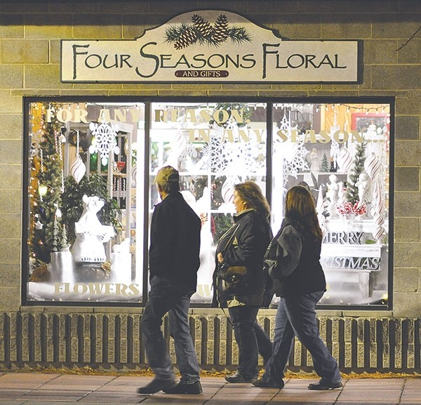 Residents walk by a festive Christmas display at Four Seasons Floral during last year's Sample the Season event.