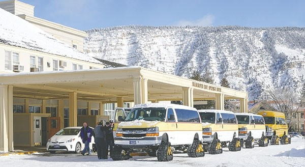 A group of snowcoaches — sporting Montana license plates — prepares to transport employees from Mammoth Hotel to the Old Faithful Snowlodge in this December 2015 file photo. Wyoming Department of Transportation officials say there's a number of commercial and personal vehicles in Yellowstone National Park that are not registered in Wyoming but should be.