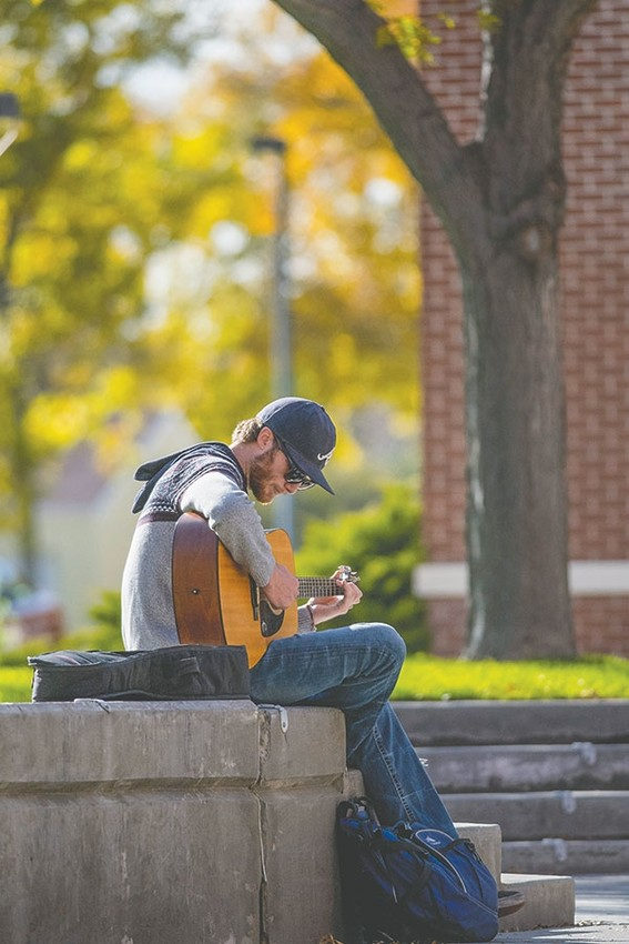 Northwest College student Adam Beck, of Lovell, takes a break after Wednesday classes to unwind on campus with a little music. Beck, a student enrolled in the business and drafting programs, is one of 1,677 students currently enrolled at NWC for the fall semester.