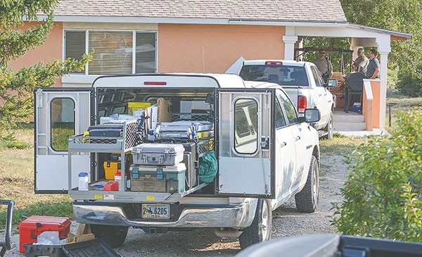 Deputies with the Park County Sheriff's Office wait on the porch of David and Shirley Williamson's Lane 11 home Saturday evening while a team from the Wyoming State Crime Lab processes the scene.