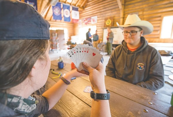 Scout leader Catherine Labdon, 21, holds a good hand as she plays cards with Lewy Harrison, 13, in a new cowboy hat. The scouts from Salisbury, England, bided their time while waiting for lunch before demonstrations on tent set-up.