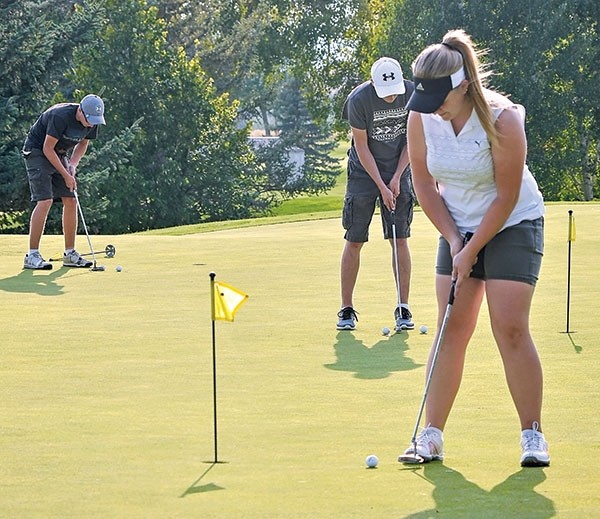 Powel High School sophomore Mycah Wainscott (in foreground), senior Treven Keeler and sophomore Crandell Sanders (at left) practice putting at the Powell Golf Club Tuesday night.