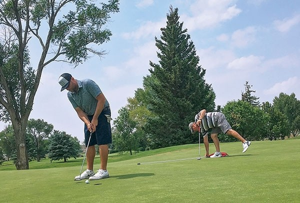 West Hernandez putts for a par on the 18th hole during Sunday's final round of the Powell Golf Club's annual club championship, while opponent Dick Fisher picks up the flag. Hernandez shot 74-72.