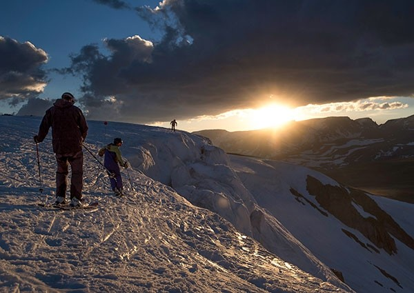 Skiers hike to a good jumping-off point for their last run before sunset at the Beartooth Basin Summer Ski Area on June 21. Heavy snow allowed the ski area to remain open into July for the first time in three years.