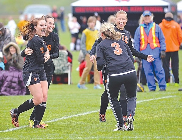 Powell High School junior Joey Haire (at left) is hugged by teammate Jalie Timmons as senior Mallory Triplett (No. 3) and Jaighden Rayment (No. 12, at right) celebrate her 45-yard goal to tie the game at 2 during Thursday's first round game of the 3A state soccer championship against Lander.