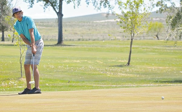 Powell High School senior Austin Asher putts the ball on hole No. 4 at Worland's Green Hills Golf Course during a Friday tournament.
