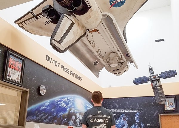 PHS student Brett Gilman stands underneath the space shuttle that he and fellow students created. Students got T-shirts designating their different roles with the project.
