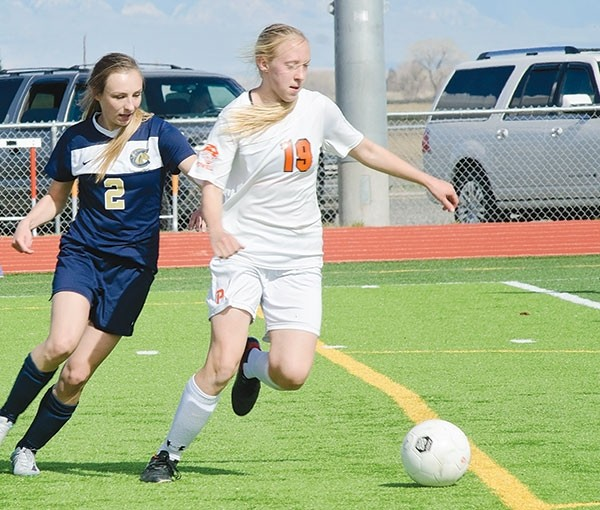 Powell High School freshman Kayla Kolpitcke (white) moves the ball up the field in a home game against Cody on Thursday, April 20.