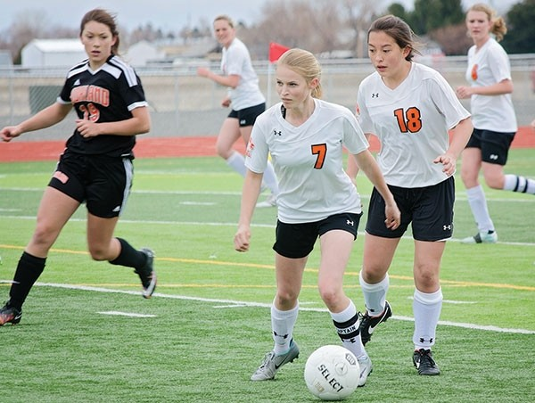 PHS's Kayla Atkinson (No. 7) looks upfield while dribbling the ball on Saturday against Worland as Ashlyn Aguirre (No. 18) moves into position.