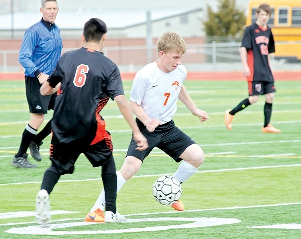 Powell High School senior Brekyn Herd (in white) maneuvers the ball around a Worland defender during a home game on Saturday.