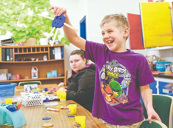Eight-year-old Dante Lauk laughs delightedly as he shows off his creation of Play-Doh and Popsicle sticks in the art room at the Youth Club of Powell on Thursday afternoon. Watching (behind) is staff member Morgan Ley.