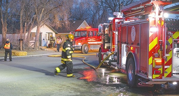 Powell firefighters and EMTs respond to the scene of a house fire on North Day Street Saturday evening. The fire rekindled Sunday morning.