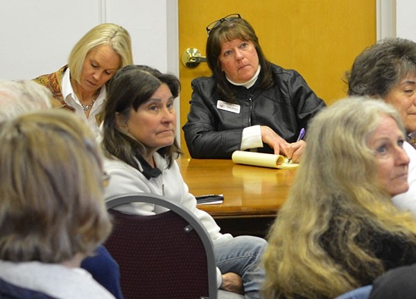 Lindy Linn, a field representative for U.S. Rep. Liz Cheney (at back left) and Pam Buline, a field representative for U.S. Sen. John Barrasso (back center), listen and take notes as a local resident shares some concerns about the Choice Act during Thursday's Congressional 'office hours' at Powell's City Hall.