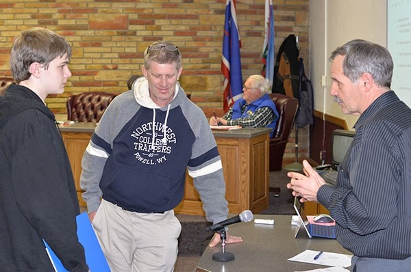 Local Boy Scout David Waite, left, and his father, Neil, talk with City Administrator Zane Logan about the upcoming Absaroka Street project at the City Council meeting Feb. 6. Waite attended the meeting to fulfill a merit badge requirement.