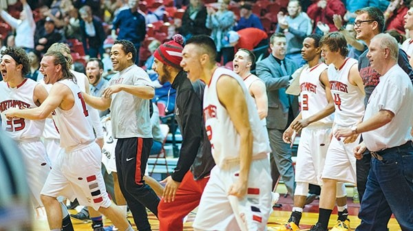 Members of the NWC men's basketball team rush onto the court to celebrate after a triple-overtime, 101-100, win on Wednesday, Feb. 8.