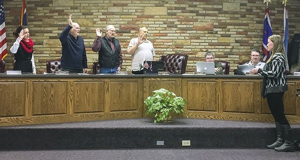 Powell City Council members (from left) Lesli Spencer, Floyd Young, Jim Hillberry and Mayor Don Hillman are sworn in Tuesday at the first city council meeting of 2017. Seated are council members John Wetzel and Eric Paul. City Clerk Tiffany Brando (far right) officiated the swearing-in ceremony. Council President Wetzel will be filling in for Mayor Hillman in the coming weeks.