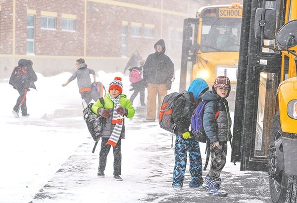 With below-zero temperatures and blowing snow, it was a frigid Friday for Powell students. Jonathan Hine (center, with orange hat), Pratt Wambeke and Calvin Opps (right) head toward the bus after school at Westside Elementary School on Friday. Pictured in the background is Mark Lynn, building custodian. Classes were canceled in Clark and the Cody school district on Friday and Monday; Powell schools stayed open.