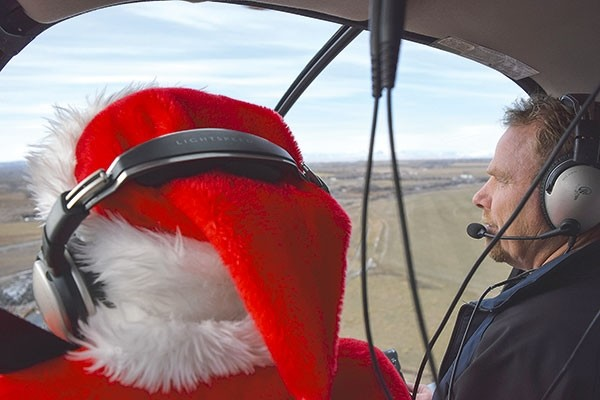 With his reindeer presumably enjoying some down time before their momentous Christmas Eve flight, Santa Claus flies toward Powell Friday morning in a helicopter piloted by Curt Abraham of Byron. Upon his arrival, dozens of children lined up to meet Santa and share their Christmas wish lists.