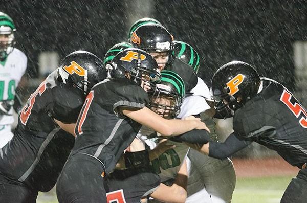 PHS senior Terrance McLaughlin (left) — alongside sophomores Carter Olsen (middle) and Cameron Schmidt (right) — bring down a Lander player during Friday's playoff win.