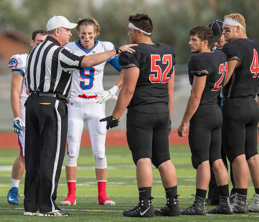 Panther captains Max Gallagher (No. 52) and Brooks Asher (No. 21) discuss the coin toss with officials before a game against Douglas last season. Gallagher and Asher will represent Powell High School in this weekend's Senior Shrine Bowl in Casper.