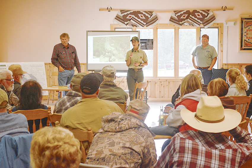 Shoshone National Forest North Zone District Ranger Sue Stresser addresses a large audience of Crandall area residents during a Friday night meeting at the Chief Joseph RV Park, while Park County Commissioner Tim French (at left) and County Engineer Brian Edwards (at right) look on.