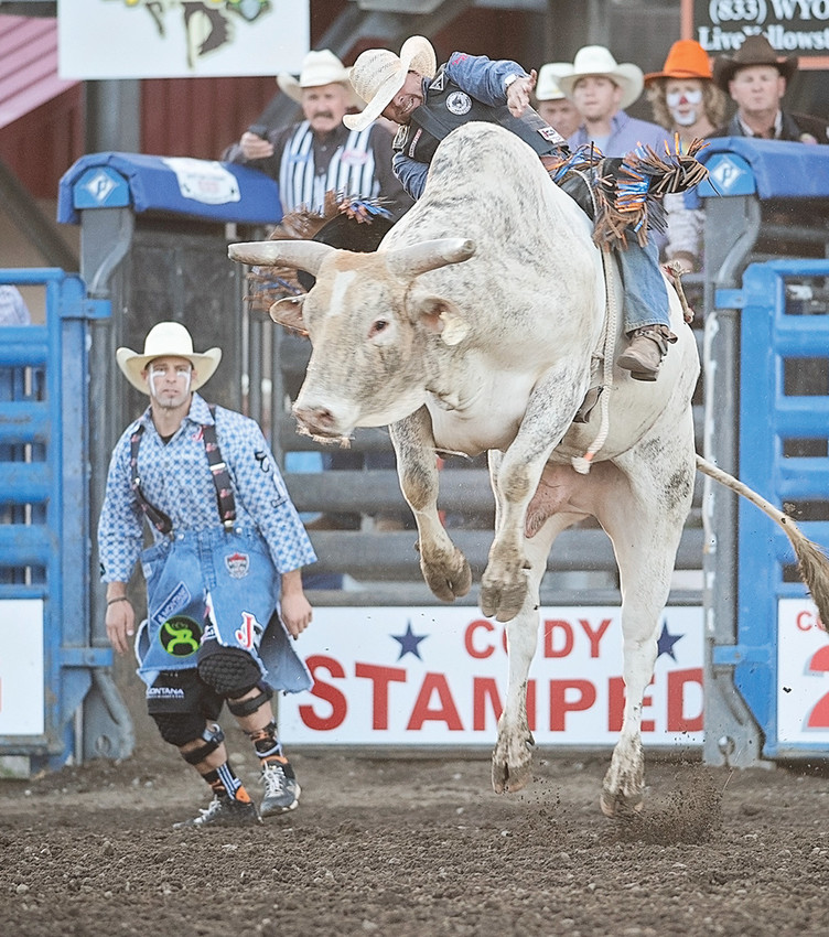 Four-time PRCA World Bull Riding Champion J.W.Harris of Goldthwaite, Texas, competes Saturday night during the Stampede Rodeo's Xtreme Bulls performance in Cody. Five-time World Champion Bullfighter Dusty Tuckness of Meeteetse is seen in the background. Harris narrowly missed the 8-second buzzer on this ride. Harris is currently 13th in PRCA's Xtreme Bulls standings .