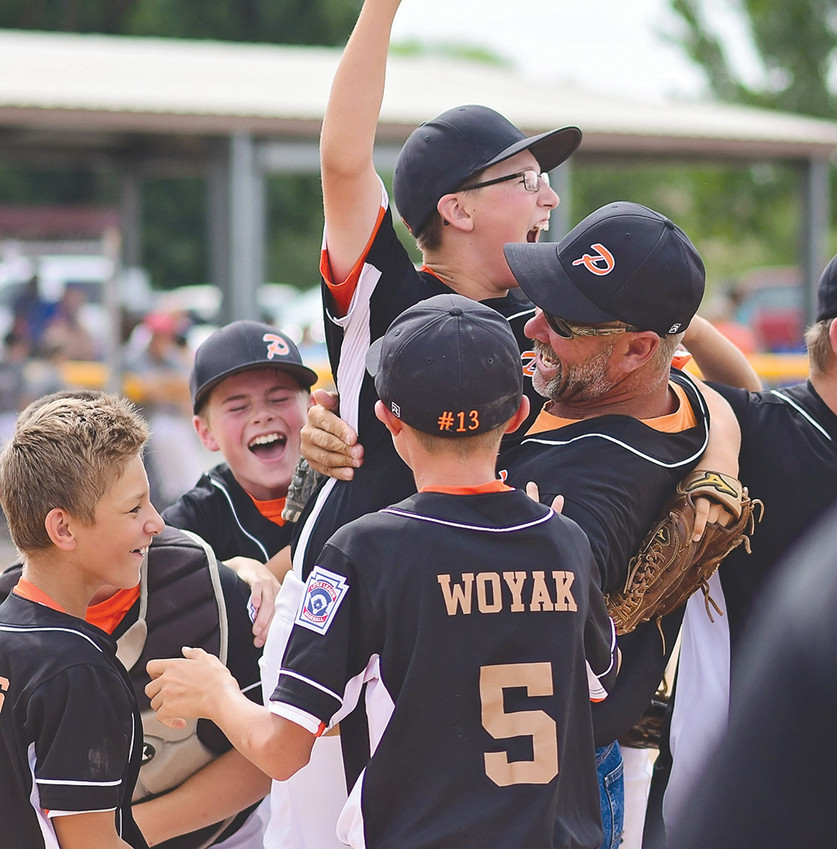 Surrounded by teammates, Powell All-Stars pitcher Cade Queen is lifted in the air by coach Heath Worstell after the final out of the District 1 Championship game. Powell won the game over Big Horn, 6-2.