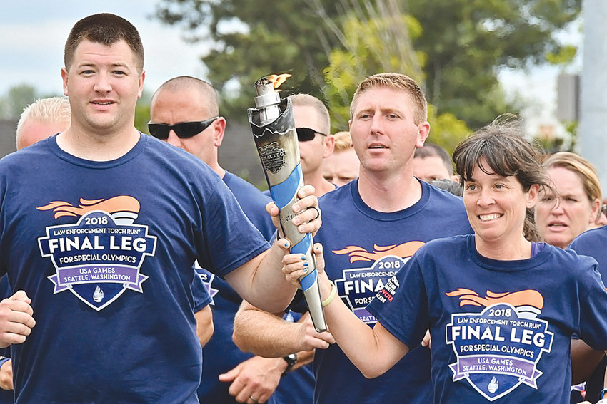 Powell Police Officer Matt Koritnik, left, helped carry the Flame of Hope to the Special Olympics USA Games in Seattle earlier this month.