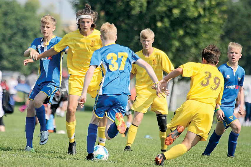 Sporting their signature yellow uniforms, Powell natives Landon Sessions (left), Lane Franks (center) and Hawkin Sweeney (No.39) surround an Iceland player during the 15U Silver Division title game at the 2018 Schwan's USA Cup soccer tournament. The Wyoming 307 side won the contest, and the championship, 3-2.