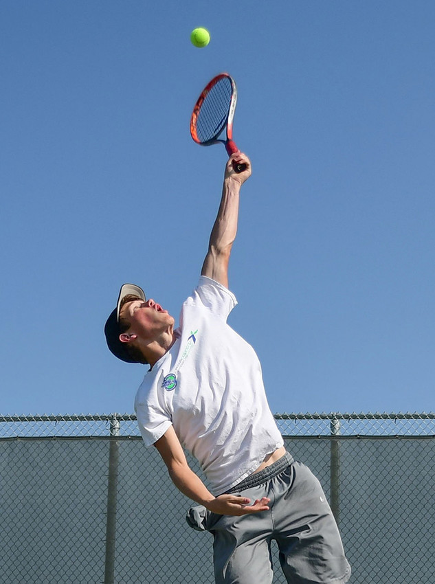 Panther junior Aiden Jacobsen practices his serve during a Saturday practice at the Powell High School courts.
