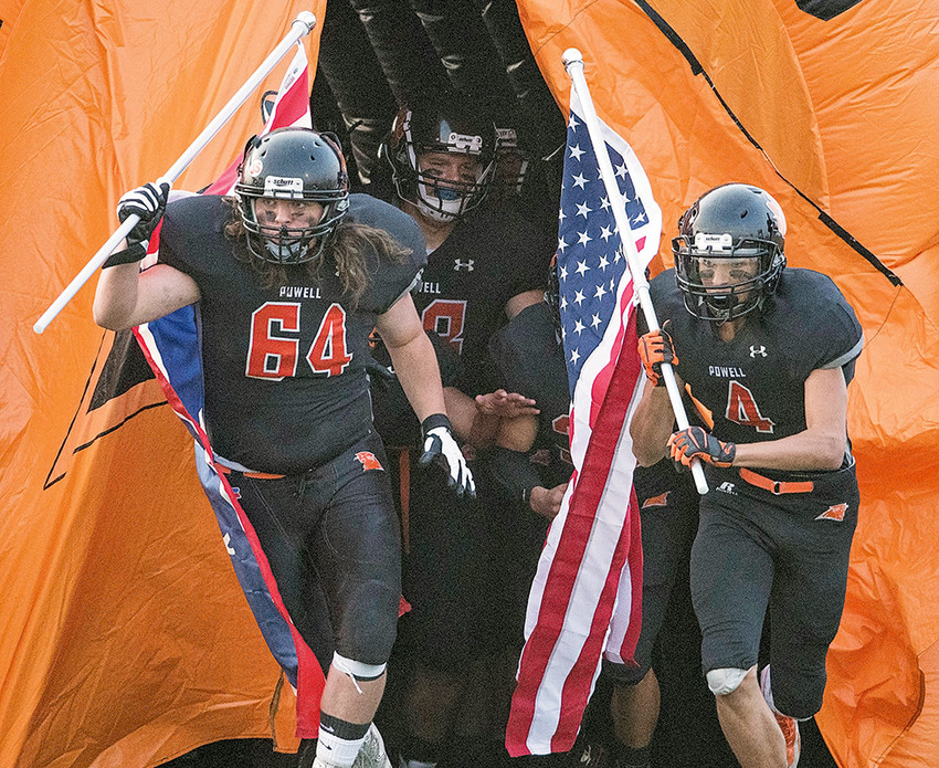PHS seniors Kain Baxter (left) and Dalton Woodward lead the team out on the field Friday against the Riverton Wolverines.