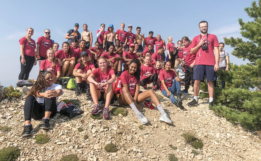 Members of the NWC athletic teams as well as other students pose at the summit of Heart Mountain on Saturday, Aug. 25. The Heart of a Trapper Run and Hike was a success, serving as the culmination of the Paint the Town Red festivities.