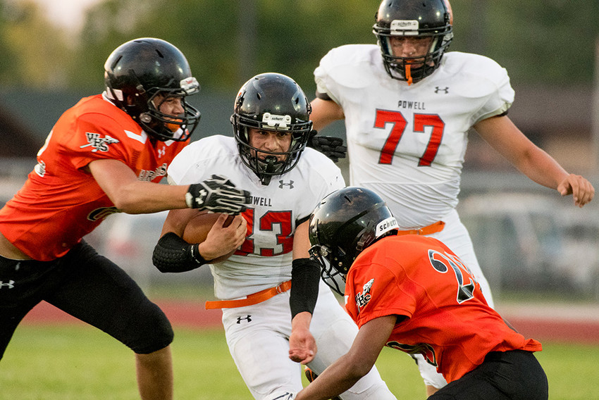 Panther running back Brody Karhu battles through a pair of Worland defenders downfield of teammate Carter Olsen looks on during Friday's game at Worland High School. The Warriors won the season-opener, 14-7.