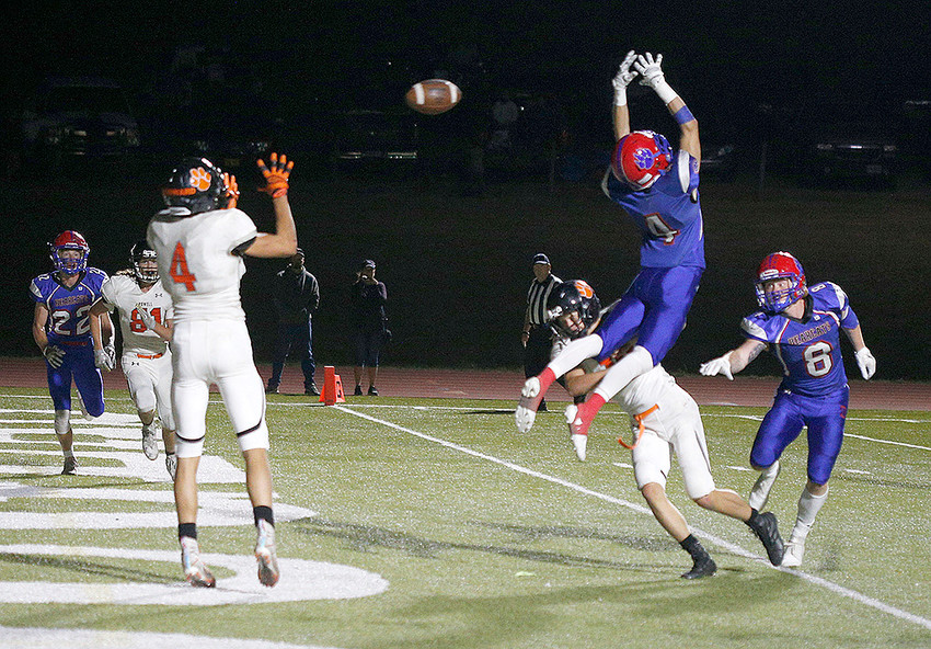 A wide-open Dalton Woodward (No. 4) catches a touchdown pass through the outstretched arms of Douglas' Colby Davidson for Powell's only score Friday in Douglas. The Panthers upset the No. 3-ranked Bearcats 7-6 for their first win on the season.