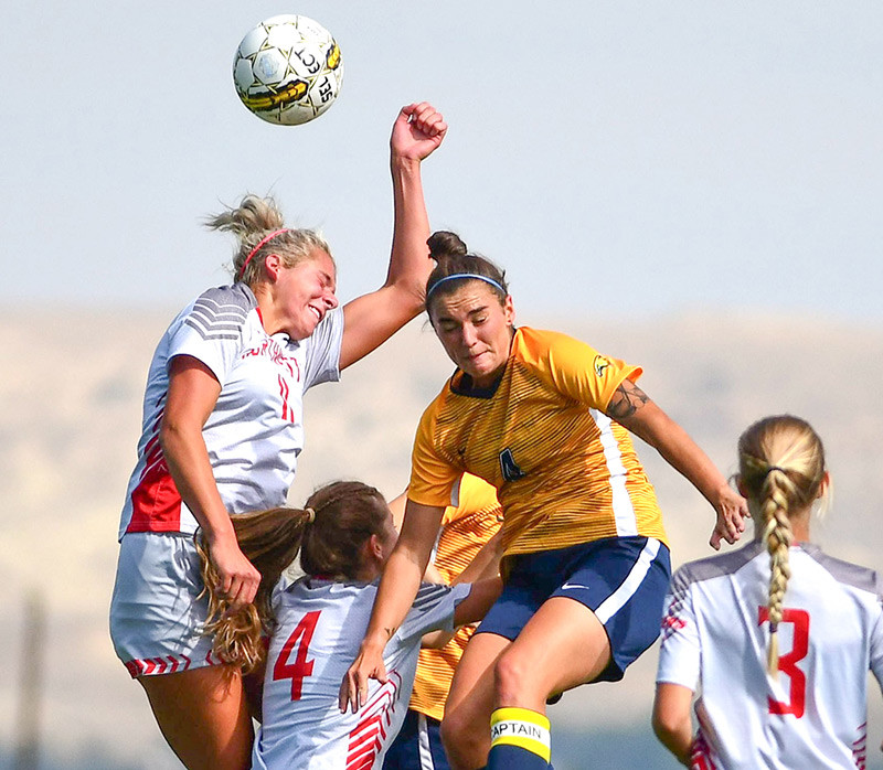 Lady Trapper Genevieve Sauers wins a header from LCCC's Annie Rolf, as teammate Brooke Seidel (4) battles for position Saturday at Trapper Field. LCCC won the contest 6-0.