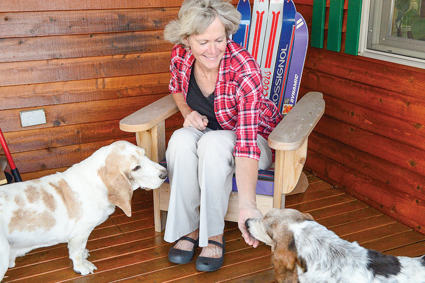 Holly Moen, director of Wyoming Basset Hound Rescue, gives her basset Oscar (right) a snack while his adopted brother Copper looks on at her residence on the South Fork.