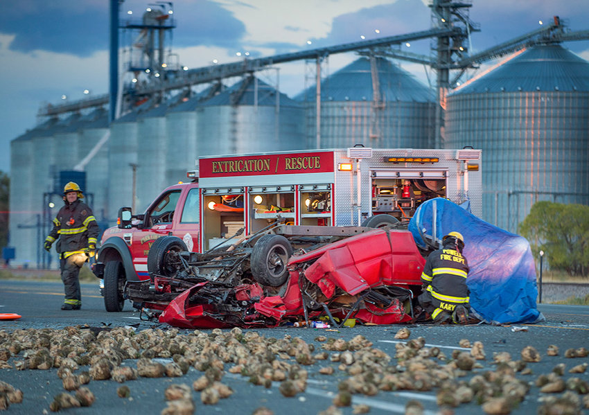 Sugar beets lie scattered across U.S. Highway 14-A, southwest of Ralston, as members of the Powell Volunteer Fire Department check the wreckage of a fatal pickup versus beet truck crash Tuesday morning. A 20-year-old man died in the incident, marking the second fatal crash in a week in the Powell area.