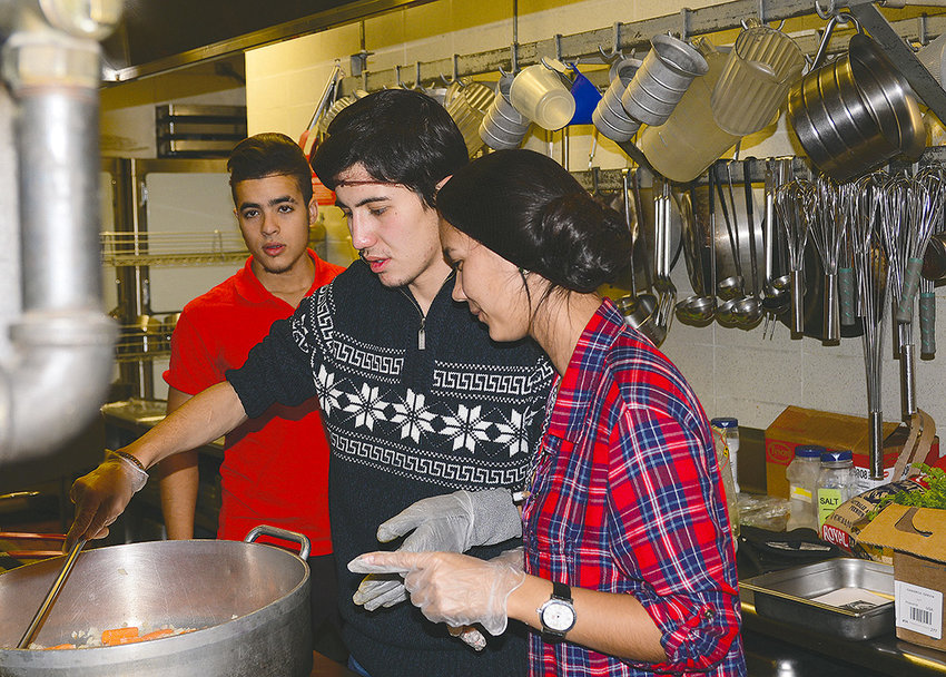 Northwest College students Tair Masharipov (center) and Bossan Abdyyeva (right) prepare pilaf for NWC's Intercultural Tuesday Lunch last week at the DeWitt Student Center as Samir Idriss looks on. Abdyyeva and Masharipov are from Turkmenistan, while Idriss is from Morocco.
